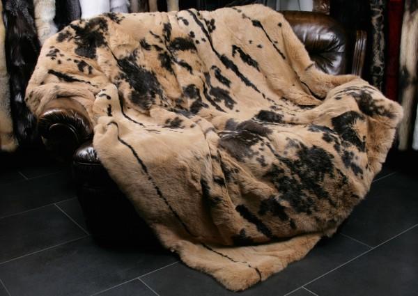 Kanin Pelzdecke in Sand mit dunklen Flecken